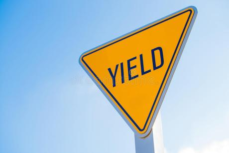 yellow-yield-sign-against-blue-sky-background-50802887