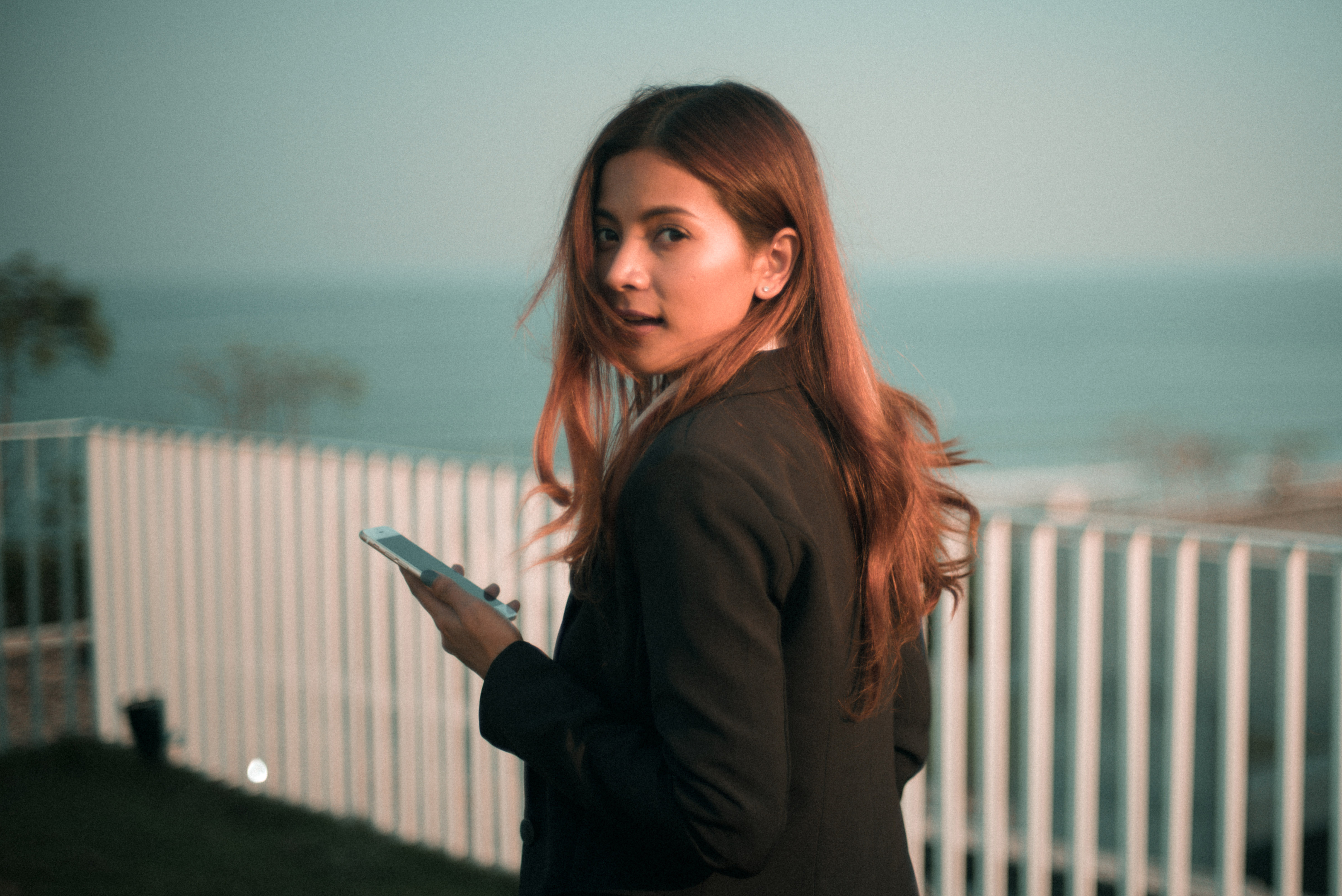 woman-looking-back-at-camera-holding-a-smartphone.jpg