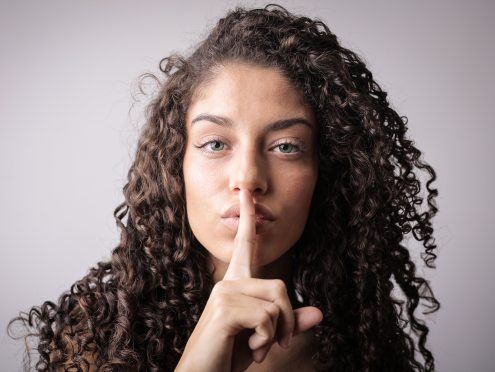 portrait-photo-of-woman-with-brown-curly-hair-doing-the-shhh-3764395